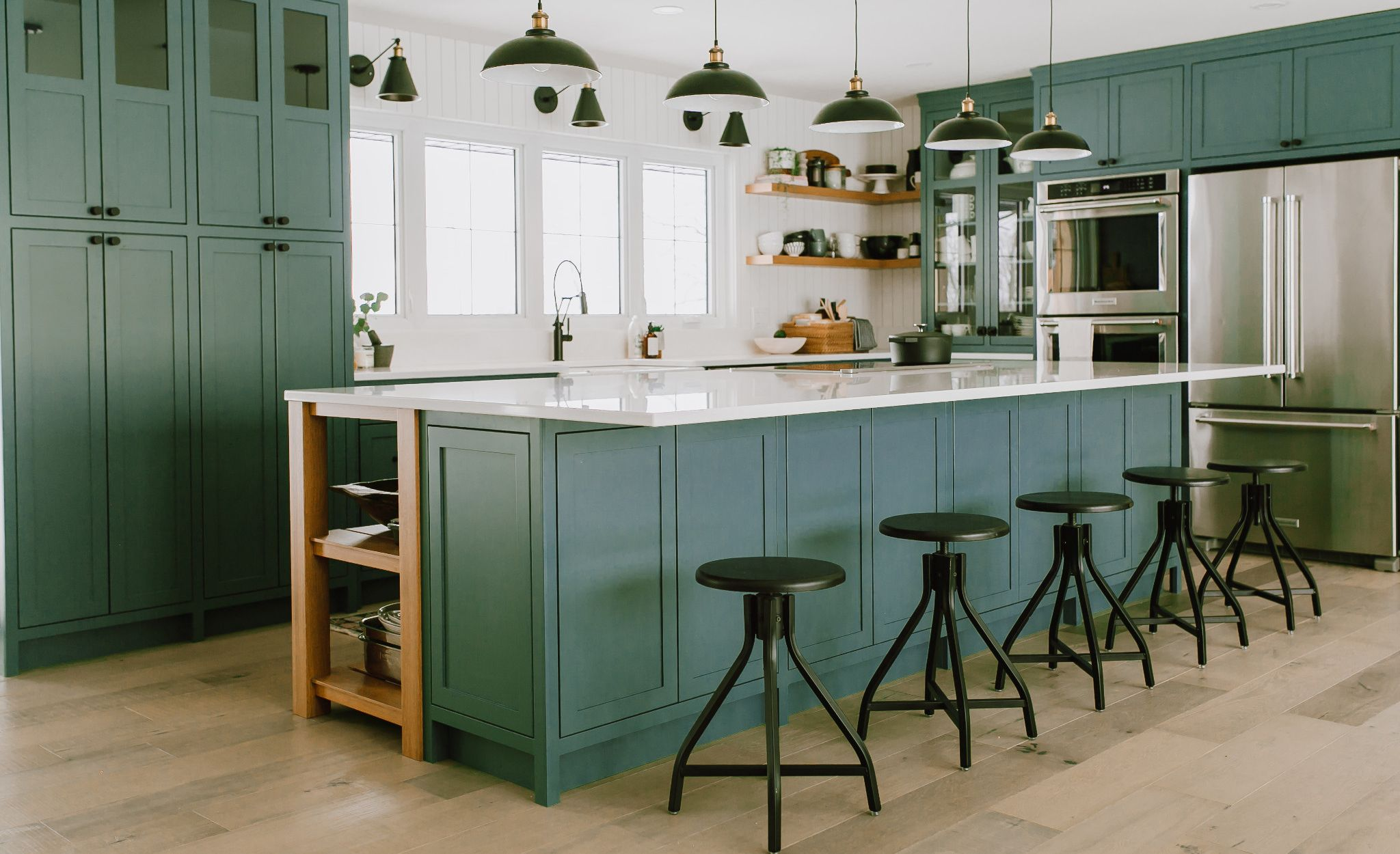 This kitchen balances airy, white walls and Cambria Newport countertops with green cabinetry and wood shelving.