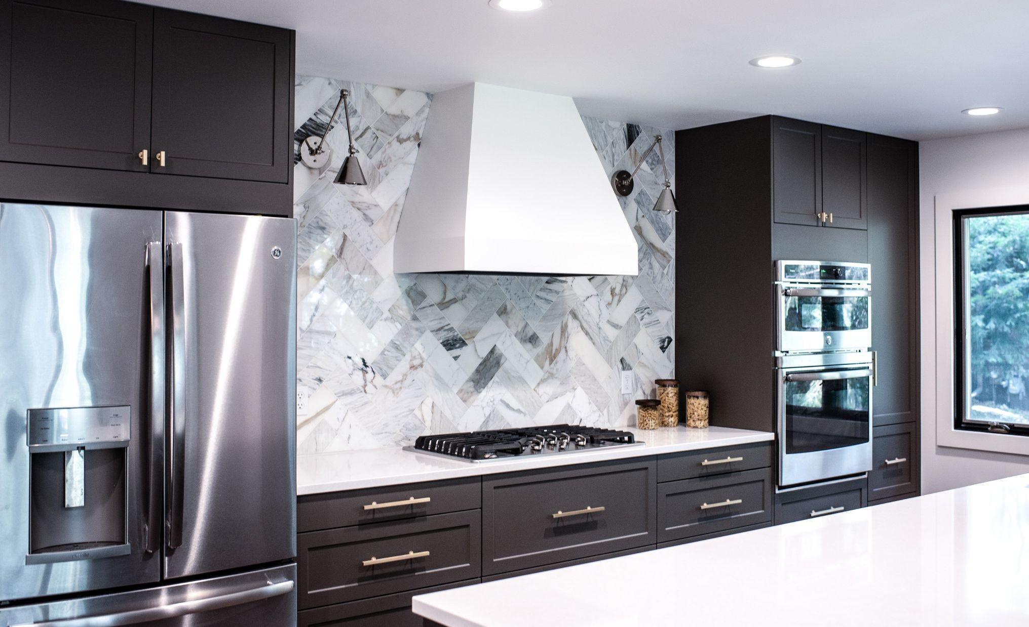 Stunning herringbone backsplash combine with Cambria Newport and gray cabinets.