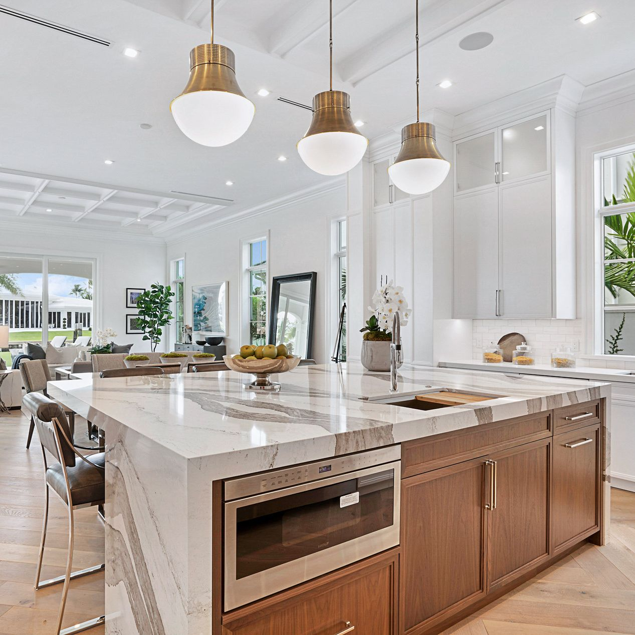 Cambria Skara Brae in a white kitchen with wood island cabinets.