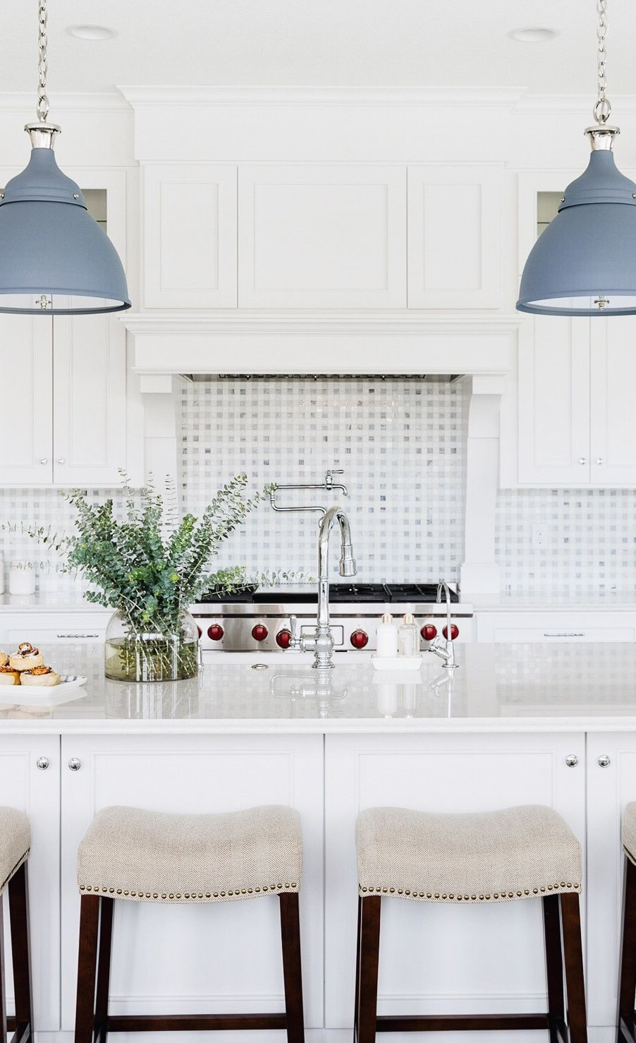 Cambria Swanbridge countertops in a white kitchen with matte blue light fixtures