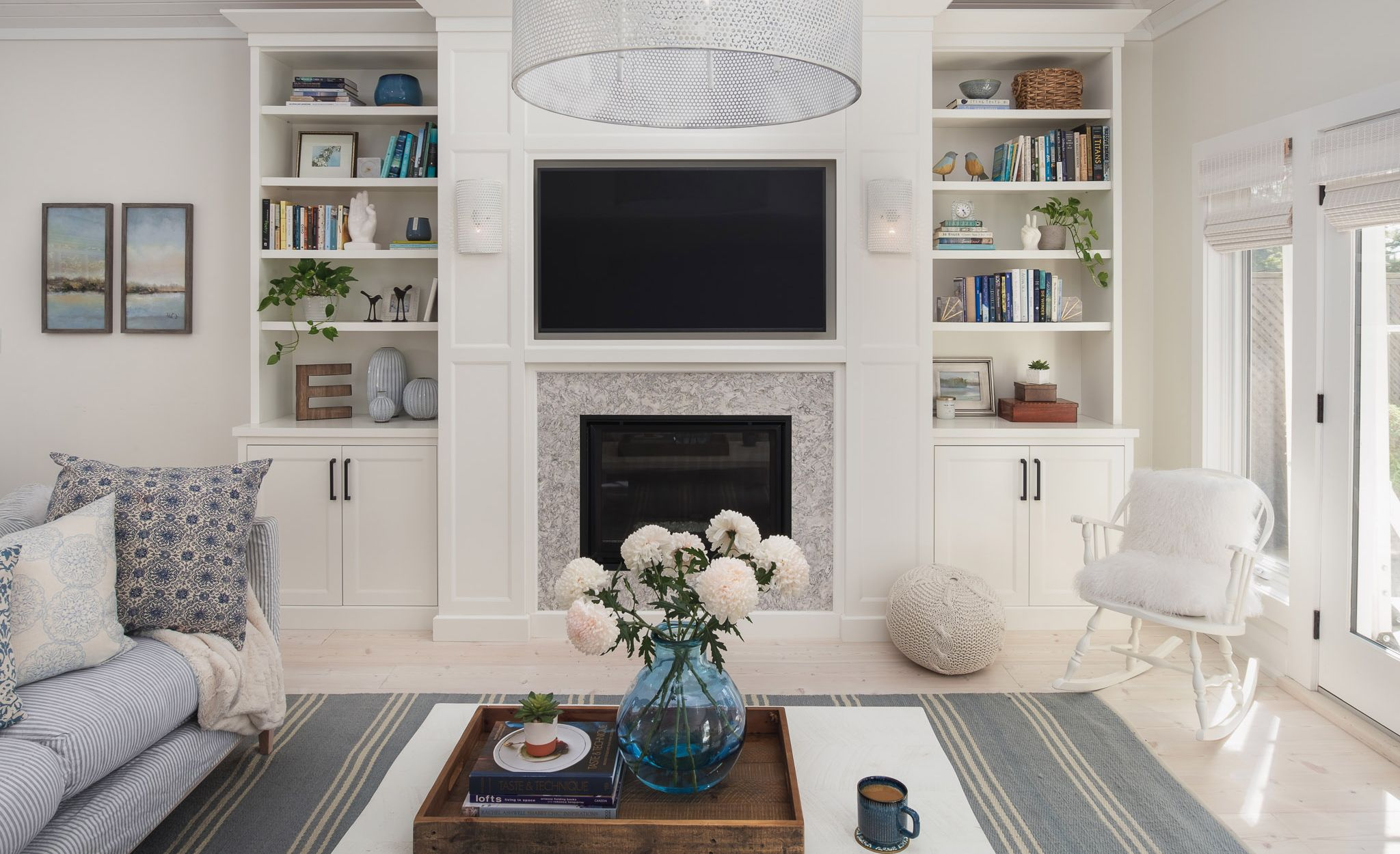 Cambria Berwyn fireplace surround paired with cabinets in a living room entertainment space.