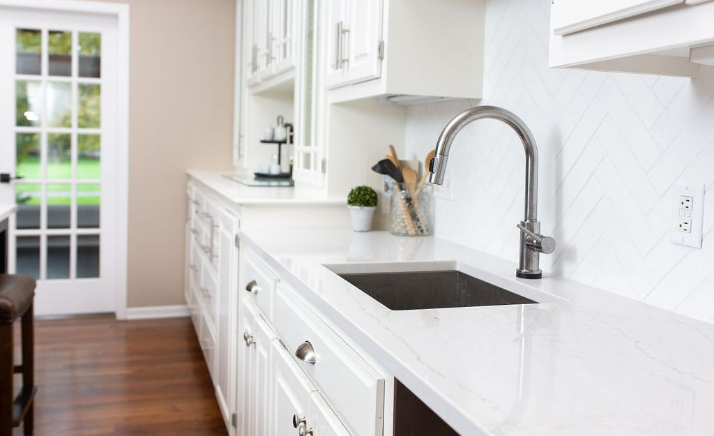 Cambria Ella countertops paired with a white herringbone tile backsplash.