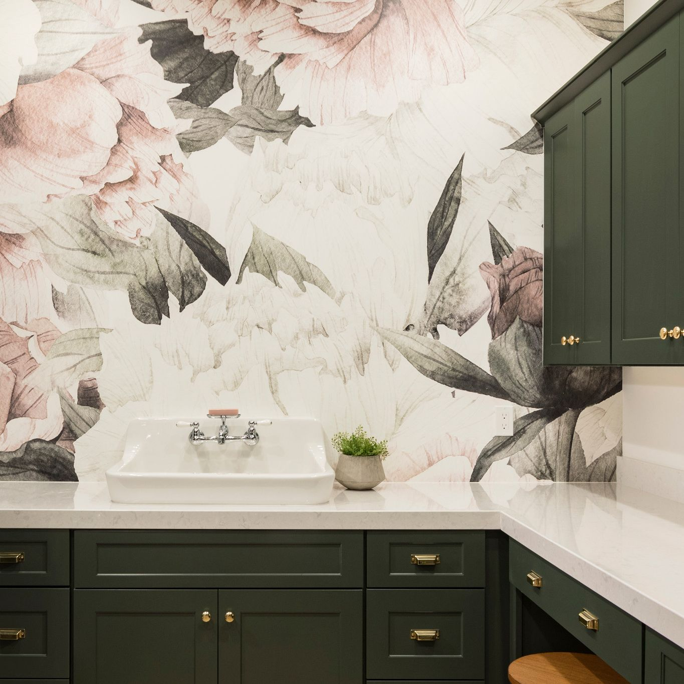 A floral mural wallpaper paired with green cabinets and Cambria Swanbridge countertops in a laundry room.
