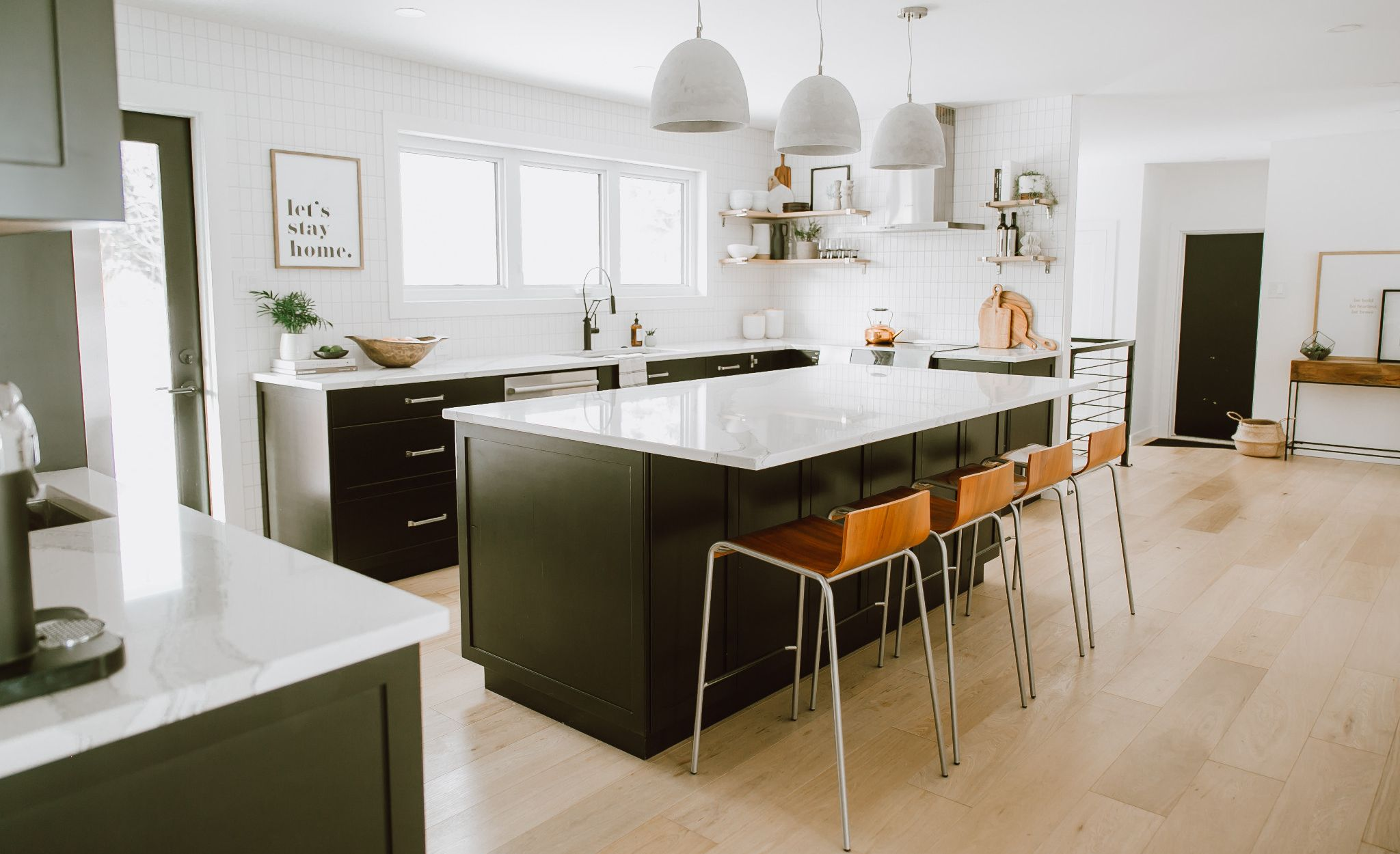 Light wood flooring and Brittanicca countertops create an open, airy feel.