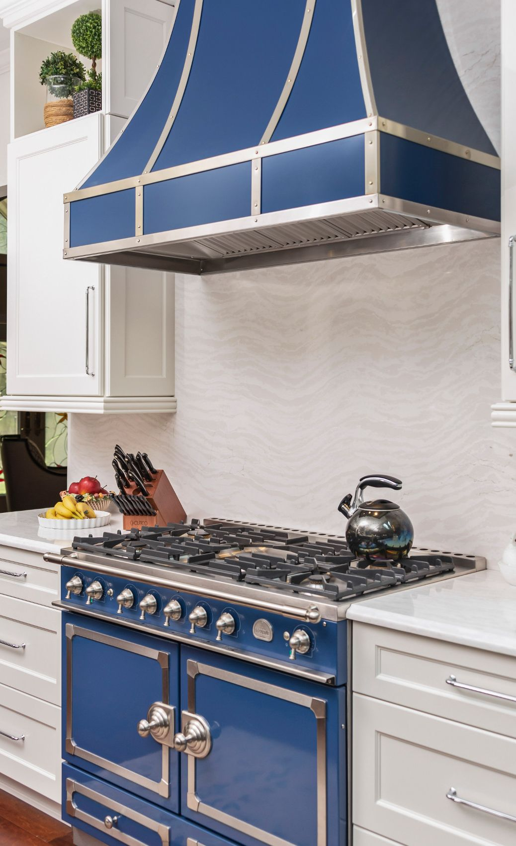 Cambria Delgatie™ creates a cascading tone-on-tone effect as a backsplash and countertops in this blue-and-white kitchen.