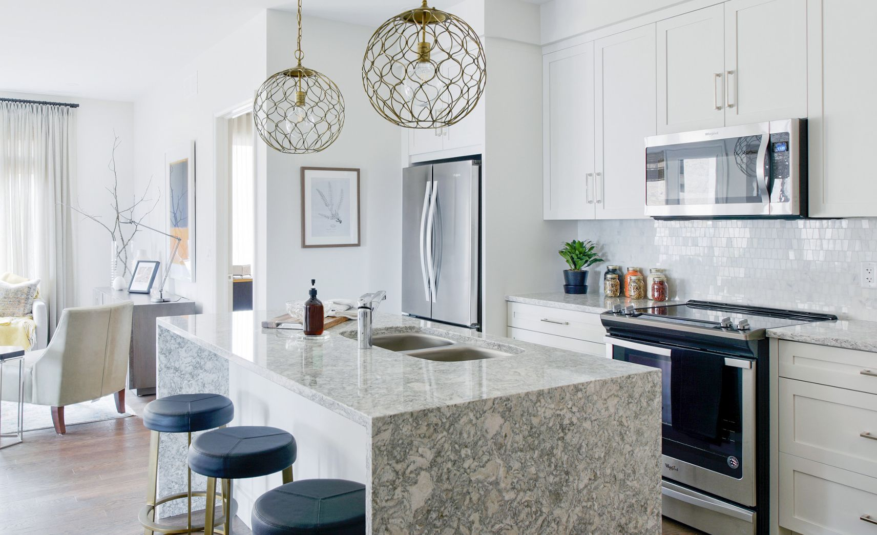 A modern kitchen stands out in this low-rise suite featuring Cambria Berwyn waterfall countertops.