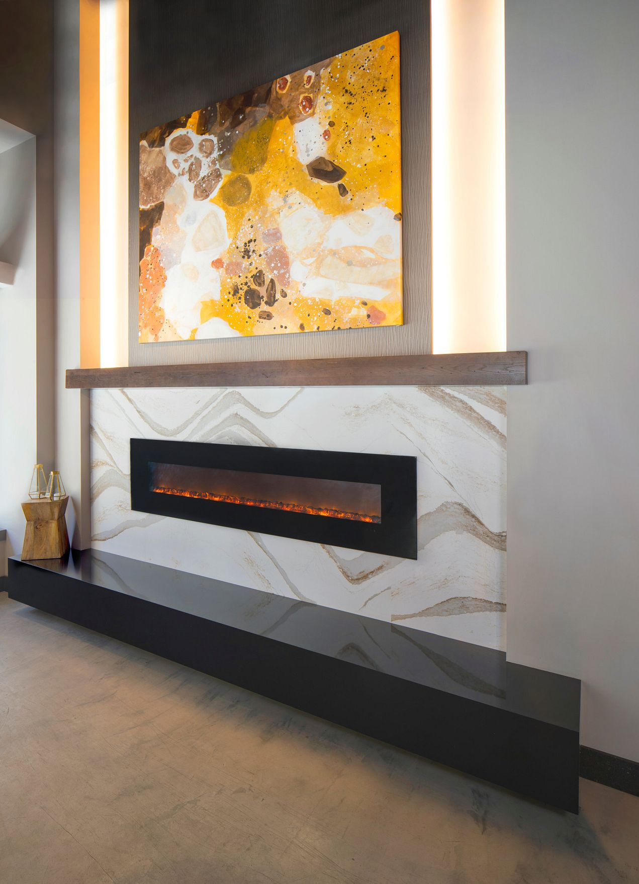 Cambria Brittanicca Gold quartz fireplace surround paired with earth tones in a commercial space.