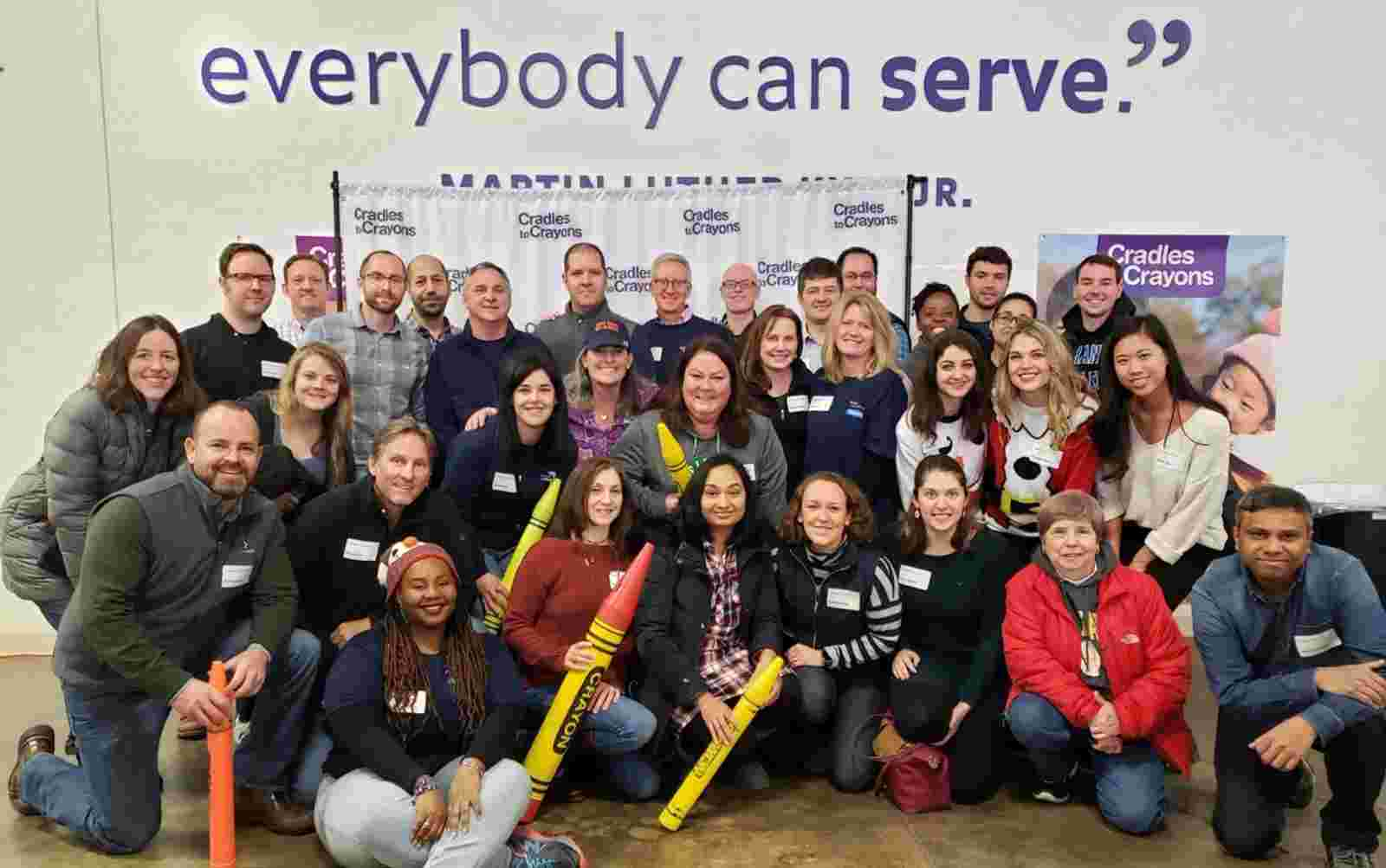 Group photo of Boston office volunteers at Cradles to Crayons event