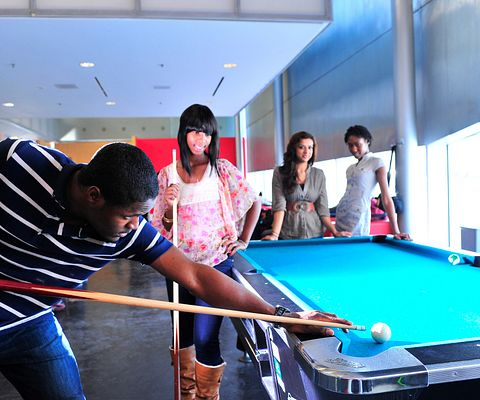 A male HYPE student takes his turn at the pool table