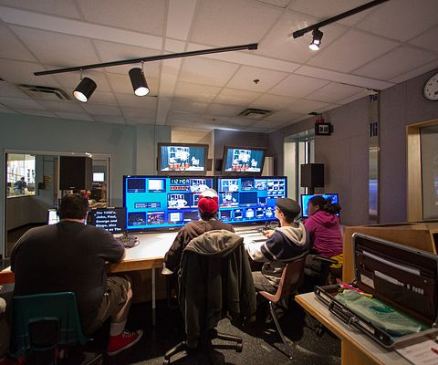 Five students of Broadcasting program are in a video control room with an array of view screens, conducting and observing a program in progress.