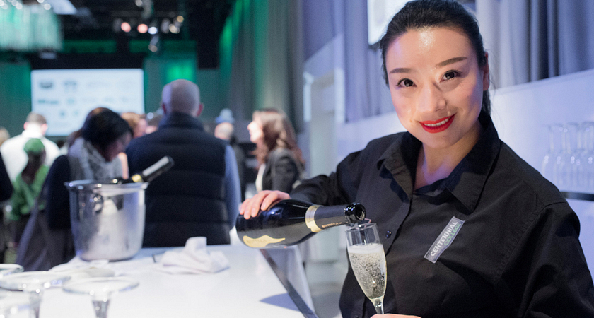 picture of a server pouring a glass of champaign at a centennial college hosted event