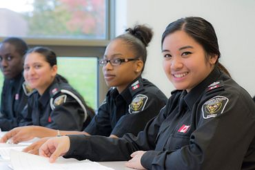 picture of Centennial College Police Foundations program students sitting in a classroom dressed in uniform
