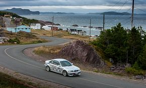Picture of a silver BMW driving in the Targa Newfoundland competition on the coast of the ocean with the centennial logo on the side