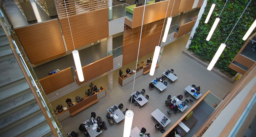 Picture of an overhead view of the Progress campus library, showing the ground-level computer desks, book shelves, balconies, and a portion of the living wall.