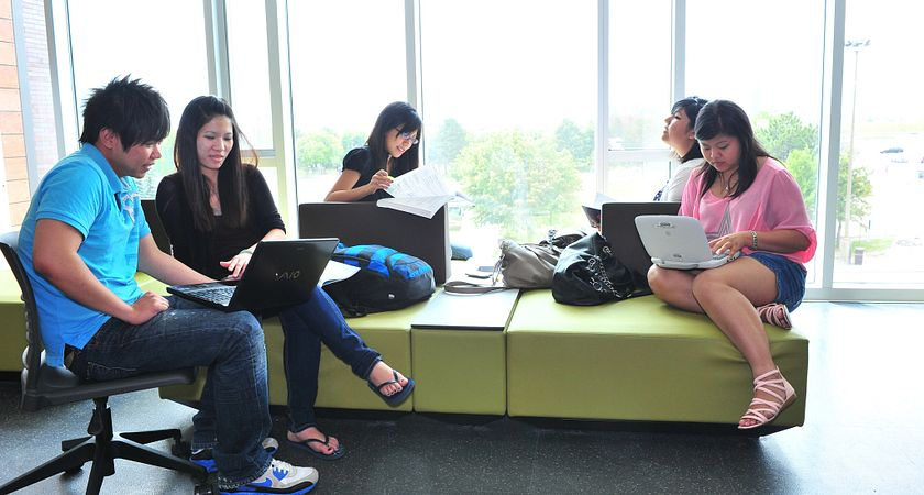 A group of students relax on a couch in the library