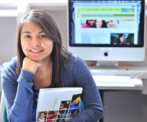 Female Aboriginal student holds a Centennial College program book, while a computer screen is on a Centennial webpage in the background