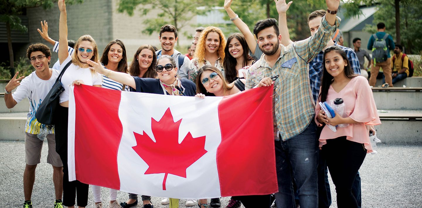 picture of Centennial College International Students holding a Canadian Flag smiling