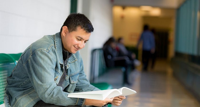 picture of a Centennial College School of Advancement Part-time Learning program student in the hall reading a book