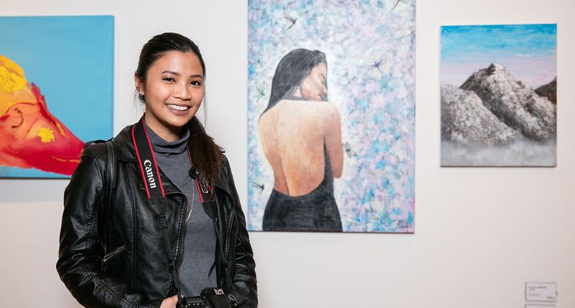 picture of a Centennial College student at an art gallery with a camera