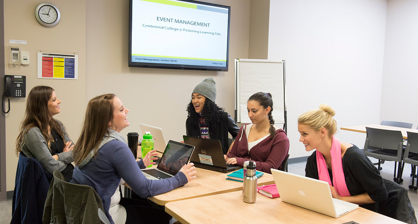 picture of Centennial College Corporate Communications and Public Relations program students working together in a meeting room