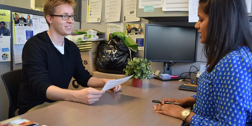 Male student happily meeting with career advisor