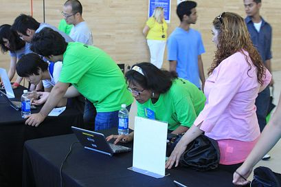 A Centennial College student ambassador looks up a new students information on a laptop during Centennial Welcomes 2012