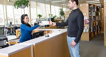 User giving a book donation to the Library