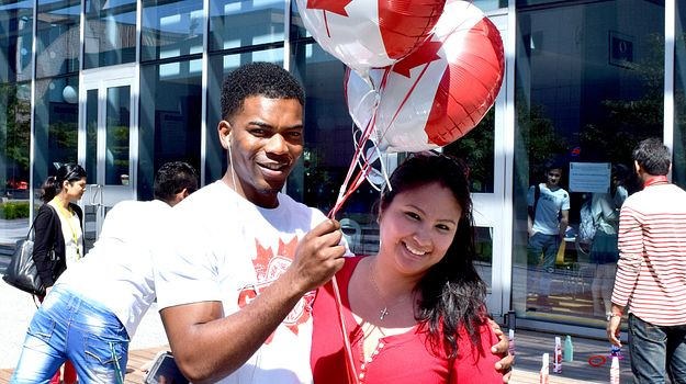 Picture of two Centennial College students dressed in red holding Canada themed balloons outside in the courtyard