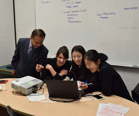 Picture of recent Led young College Marketing Research and Analytics graduates Angela Ju, Heather Ryan and Alina Wang working on a laptop together as a group