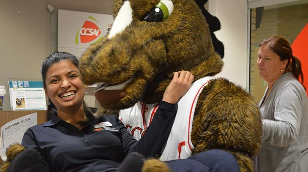 Picture of CCSAI President Deepika being carried by Centennial College's Mascot the Wonder Colt at Centennial Welcomes.