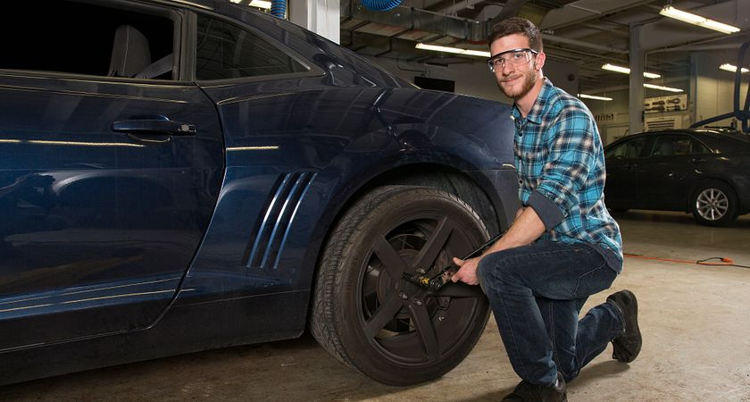 picture of a Centennial College Automotive student changing a tire on a car in a garage