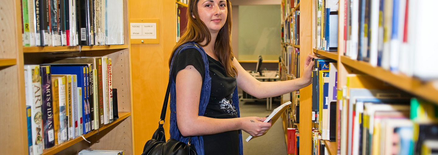 Centennial student getting a book from a shelf