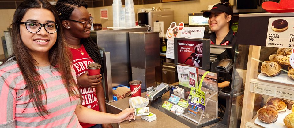 picture of a Centennial College student ordering a coffee from an on-campus Tim Hortons