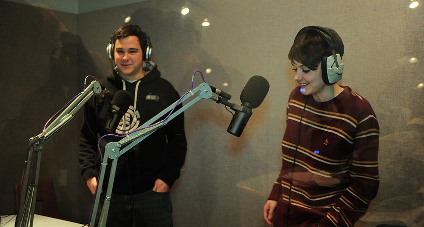 Picture of two Broadcasting and Film students wearing headsets and standing in front of microphones in a sound-proof room in the recording studio at the Story Arts Centre