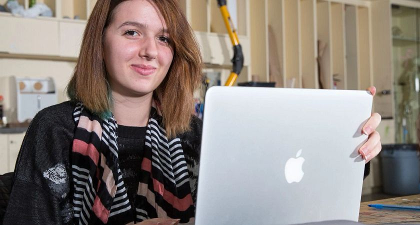 picture of a Centennial College Graphic Design program student working on their laptop in an on-campus studio