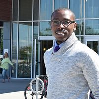 Picture of centennial college child and youth worker graduate kwesi johnson standing outside the progress campus library