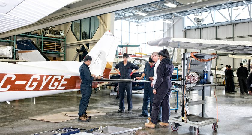 picture of Centennial College students working in a hangar on an airplane