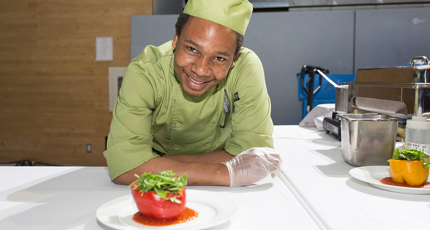 picture of a centennial college culinary student standing with a dish they prepared