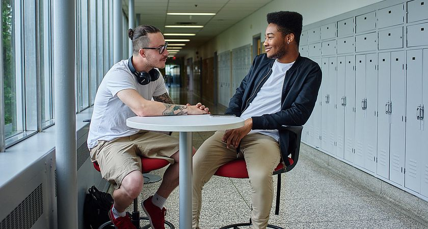 Two male students talking around a table