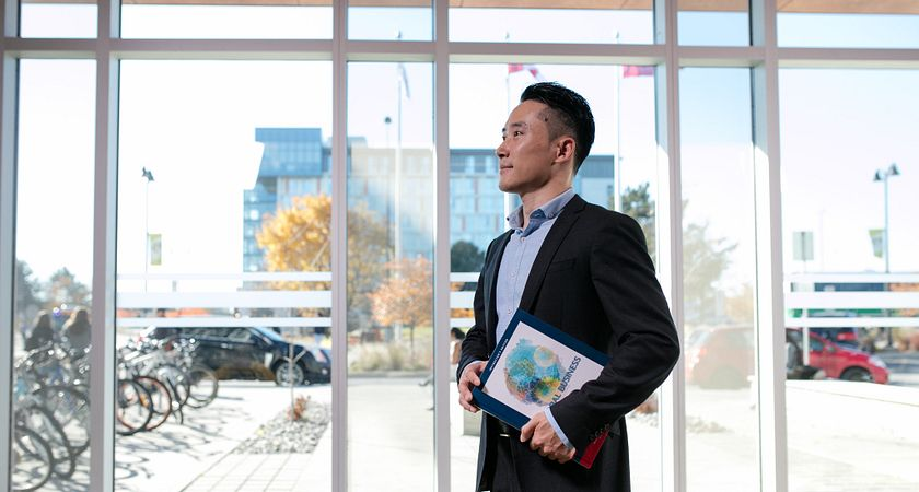 picture of a Centennial College International Business Management program student dressed in business professional holding a textbook in the Progress Campus library