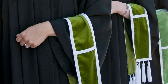 Picture of Centennial College graduates arms holding a graduation ceremony scarfs
