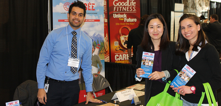 Picture of students smiling while holding pamphlets beside a job fair vendor
