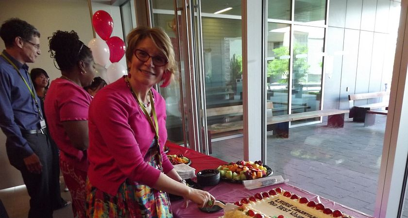 Picture of Laurie Malabar cutting cake at her retirement party