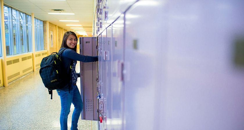 Female Aboriginal student reaches inside a locker as she carries her backpack in one shoulder