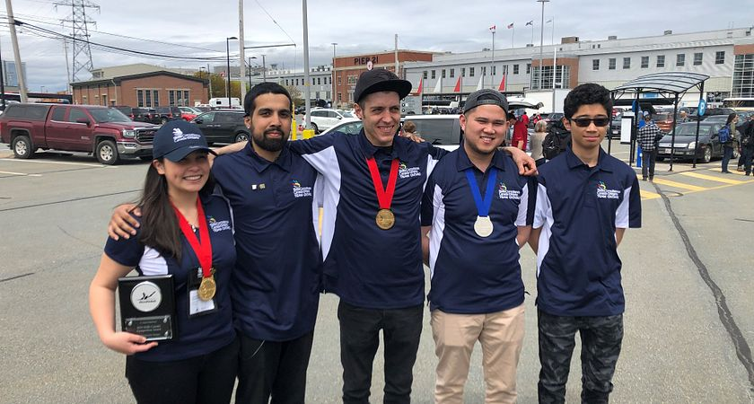 Picture of students from Team Centennial wearing their medals at Halifax's historic Pier 21