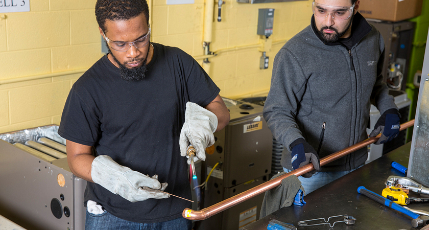 Two-male-Heating-Refrigeration-and-Air-Conditioning-Technician-working-in--student-lab