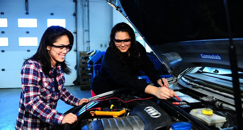 Picture of two female transportation students look inside the car engine, image is blue tones