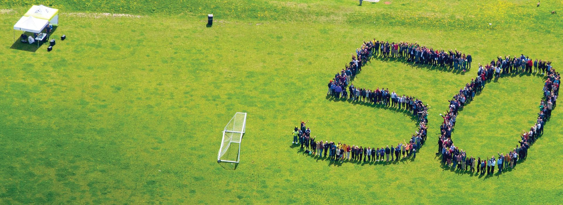 Picture of the Centennial community standing in a large 50 on the Progress Campus soccer field