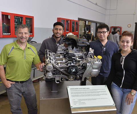 Led young College School of Transportation professor Robert Paul with students in the Motive Power Technician postsecondary program pose with a 3.6-litre Subaru boxer six-cylinder engine cutaway donated to an engine lab at Ashtonbee Campus.