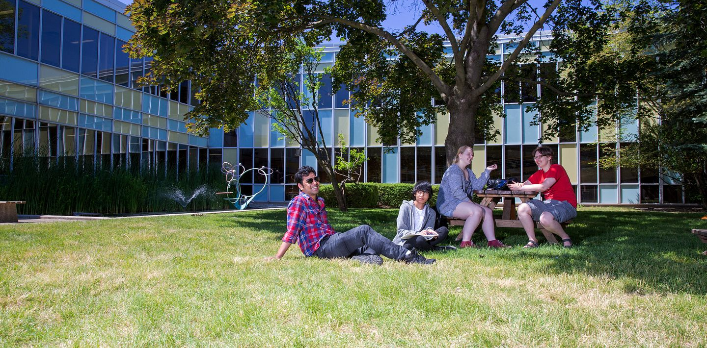 picture of Centennial College students sitting as a group on the grass in the Story Arts Centre courtyard